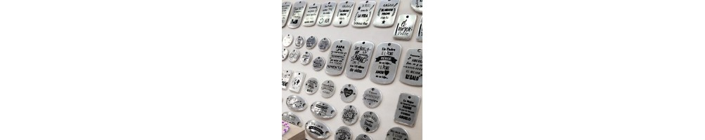 Colgantes y conectores de zamak grabados con mensajes y textos pre-diseñados.